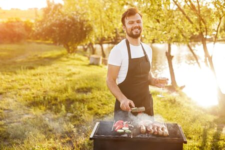 Delighted male preparing barbecue on brazier on nature
