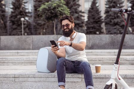 Smiling hipster using smartphone on street