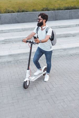 Hipster with electric scooter standing on pavement