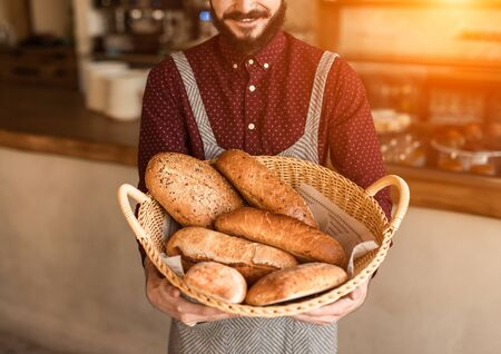 Crop baker with basket of bread Archivio Fotografico - 130114768