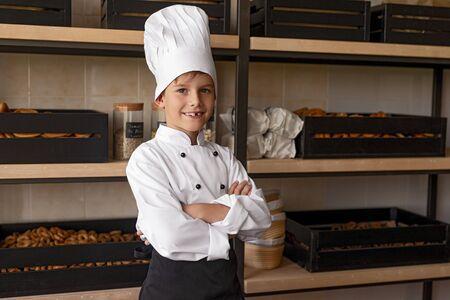 Positive little baker standing near shelves