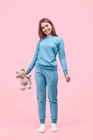 Smiling teenager with teddy bear
