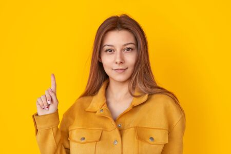 Stylish woman in yellow jacket pointing up