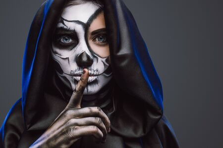 Female with spooky painted face and finger on lips