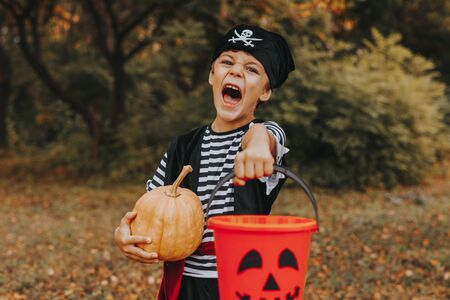 Disguised kid standing with pumpkin and bucket