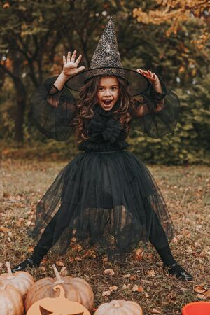 Little witch on Halloween Day in park