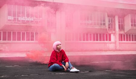 Trendy young female in pink smoke