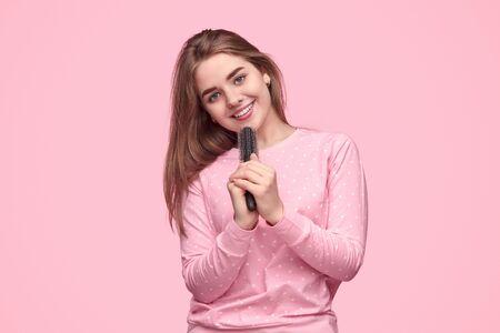 Adolescente sonriente cantando en peine