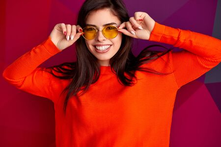 Stylish female in yellow glasses and red outfit