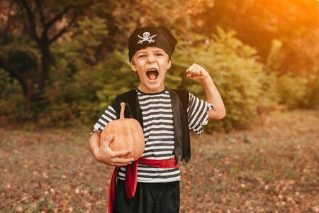 Excited pirate with pumpkin screaming in park 版權商用圖片