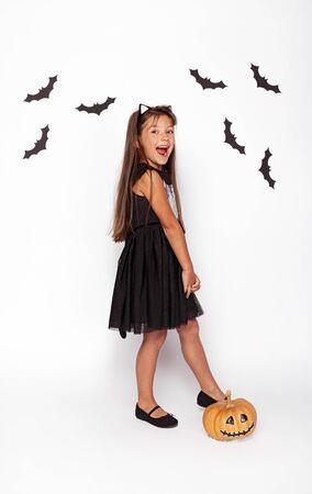 Joyful girl with pumpkin and paper bats 版權商用圖片