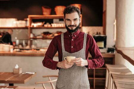 Bearded barista with cup of coffee in cafe