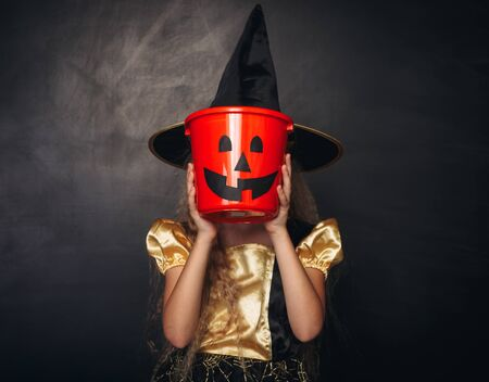 Little witch covering face with candy pumpkin bucket