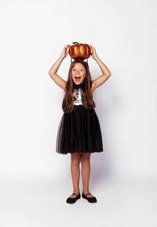 Funny girl with painted pumpkin on head