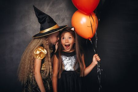 Funny children in Halloween costumes sharing secret 版權商用圖片
