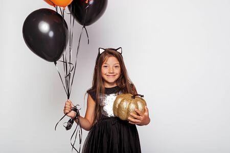 Cute girl with air balloons and pumpkin 版權商用圖片