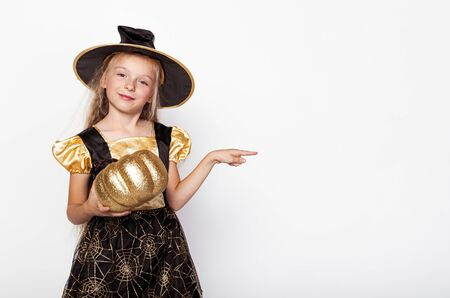 Girl with golden pumpkin pointing away
