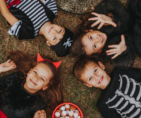 Cheerful friends lying on lawn on Halloween Day