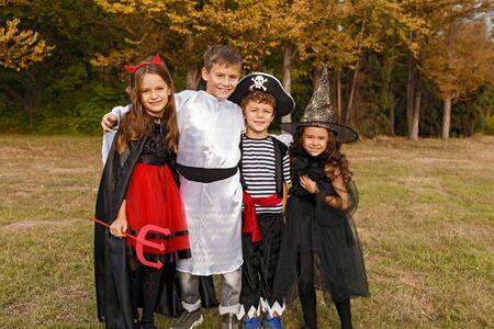 Adorable kids in Halloween costumes hugging in field 版權商用圖片