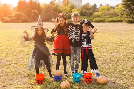 Scary cute children in Halloween costumes standing in field