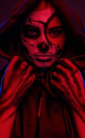 Female skeleton adjusting hood under red light