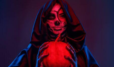 Spooky lady with pumpkin celebrating Halloween 版權商用圖片
