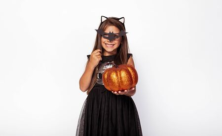 Happy girl with bat mask and shiny pumpkin