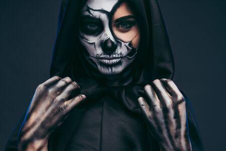 Mysterious woman adjusting black hood