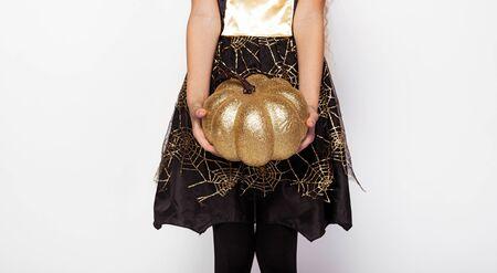 Faceless kid with sparkling pumpkin