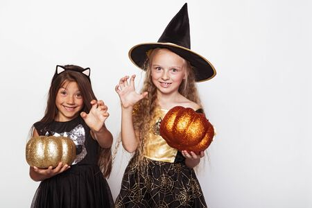 Funny girls in carnival costumes with pumpkins