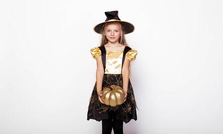 Little witch holding decorative golden pumpkin 版權商用圖片
