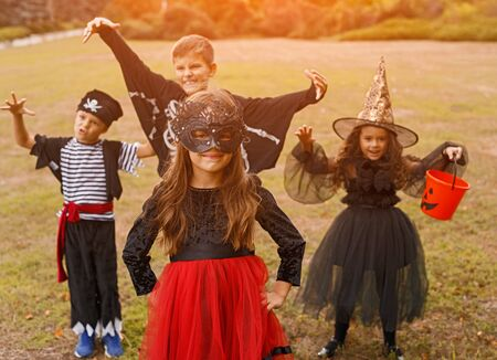 Adorable kids in carnival costumes playing on nature background Фото со стока