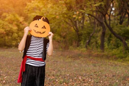 Little boy in Halloween costume standing in autumn forest 版權商用圖片