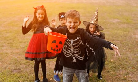 Little skeleton trick or treating with friends Banco de Imagens