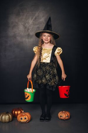 Little witch with colorful pumpkin buckets