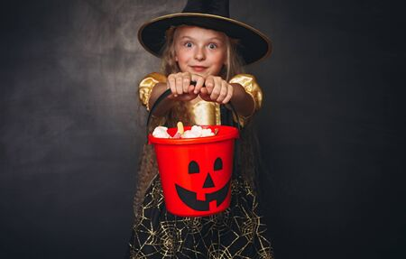 Amazed little witch with red pumpkin bucket