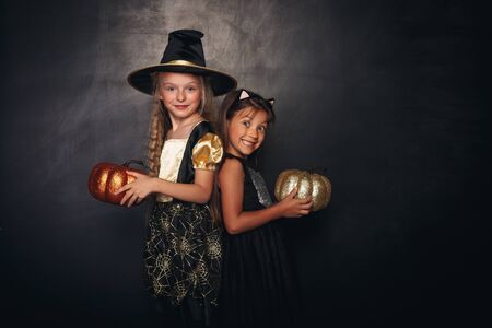 Pretty girls with stylish shiny pumpkins
