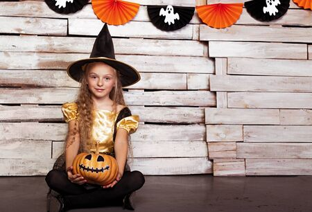 Little witch sitting with pumpkin by decorated wall
