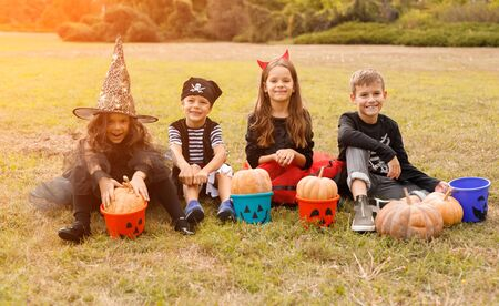 Funny kids with pumpkins and buckets on daytime