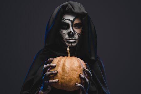 Spooky woman with pumpkin celebrating Halloween