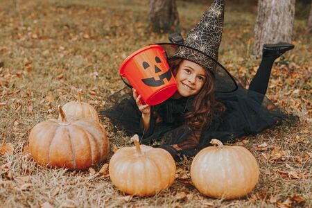 Cute girl with pumpkins and empty candy collector