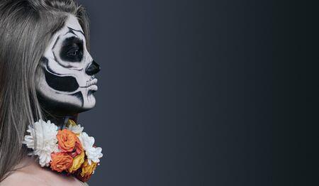 Mujer espeluznante con cara pintada y flores. Foto de archivo