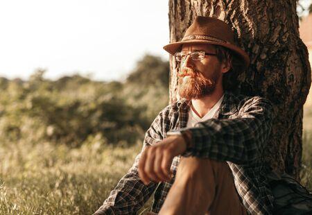 Thoughtful traveler resting near tree 版權商用圖片