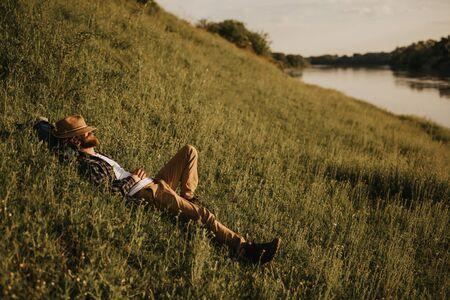 Male traveler resting on hill near river 版權商用圖片