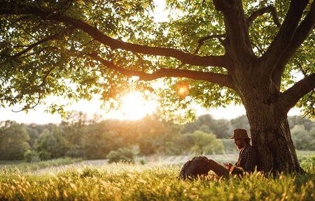 Hiker using smartphone under tree 版權商用圖片