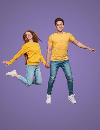 Cheerful couple jumping together and smiling