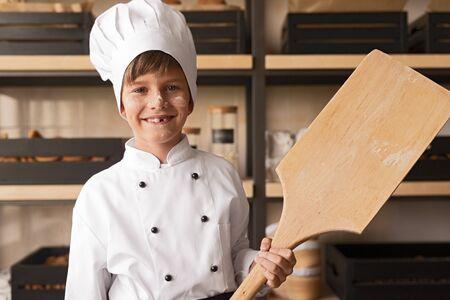 Cheerful kid in cook uniform with shovel in bakery 版權商用圖片