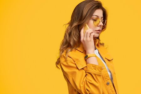 Attentive woman in bright clothes talking on phone 版權商用圖片