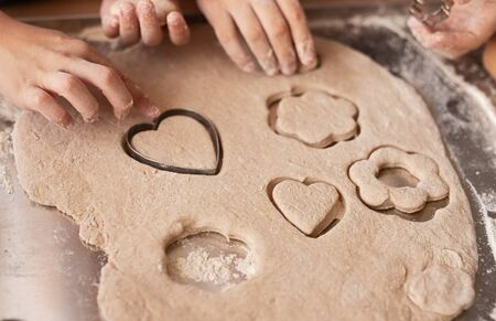Anonymous kids cutting cookies from dough