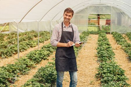Smiling farmer making notes in hothouse 版權商用圖片